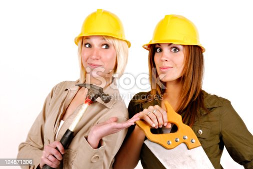 Two Women. Yellow Hard Hats, Hammer, Saw. Expressive Smiles and Wide Eyed Look! Dressed in Jackets. One Blonde and One Red Head/Brunette.