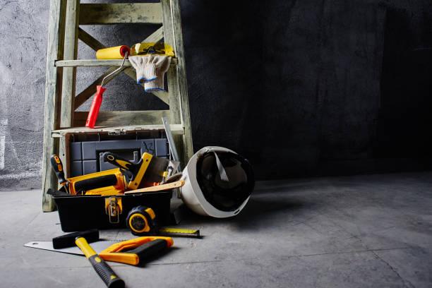 Bau-Tools und Trittleiter auf eine schwarze Wand Hintergrund. Reparaturen – Foto