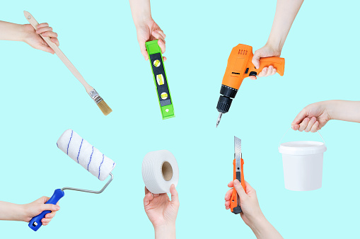 Construction tools in hands for improvement and home repair on a green background.