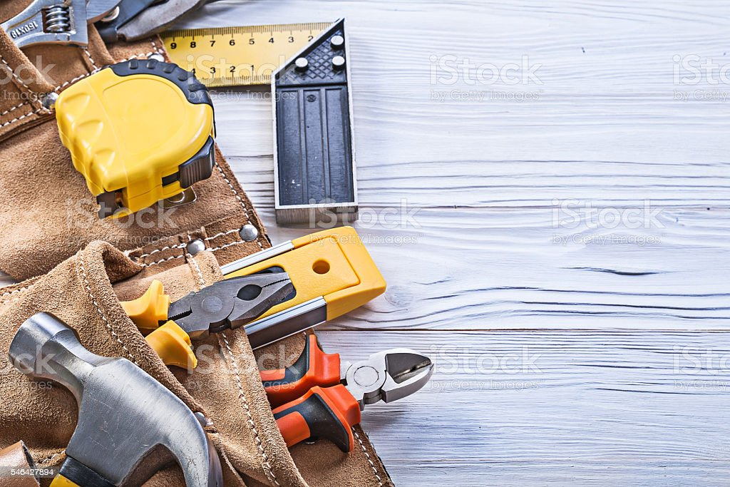Construction tools in leather building belt on wooden board main stock photo