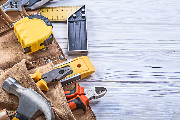 construction tools in leather building belt on wooden board main - tool belt stock photos and pictures