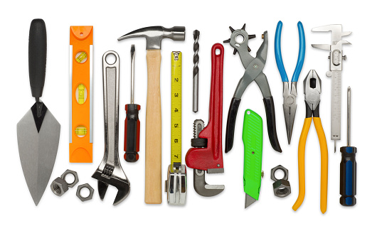 This is an overhead photo of construction tools isolated on white background. There is a level, nuts, ranch, screwdriver, hammer, tape measure, drillbit, plumber's wrench, rivet hole puncher, razor blade, pliers, measuring tool, and more.