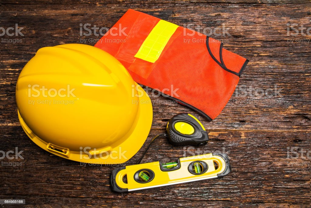 Construction tools or safety equipment with yellow helmet on wooden table. stock photo