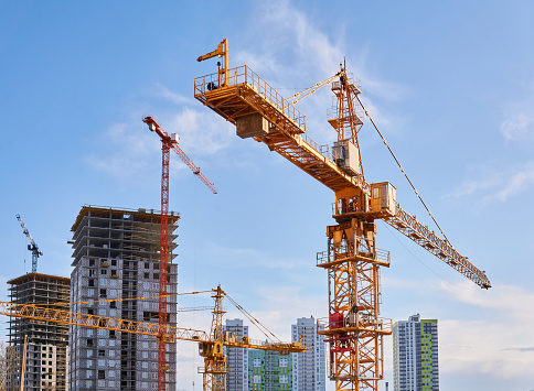 several construction tower cranes of different heights at a building site during the construction of blocks of flats, view against the sky