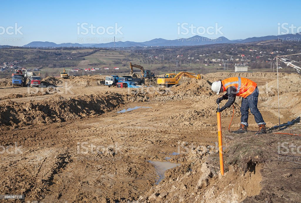 Construction trucks and engineer at dig site royalty-free stock photo