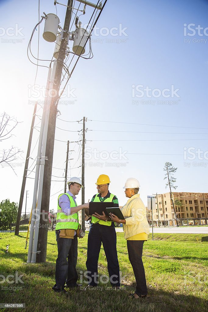 Construction, utilities workers, supervisors talk at job site. stock photo
