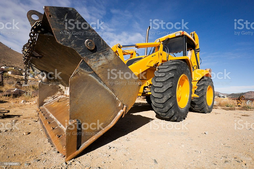 A construction vehicle with four wheels and front end loader royalty-free stock photo
