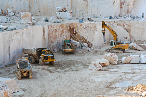 Construction vehicles working in marble quarry with oversized marble blocks
