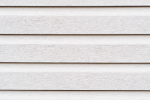 Construction vinyl siding panels pattern. House covered with white plastic vinyl siding. Vinyl siding wall surface with horizontal lines texture background. Wall covered with plastic beige siding.