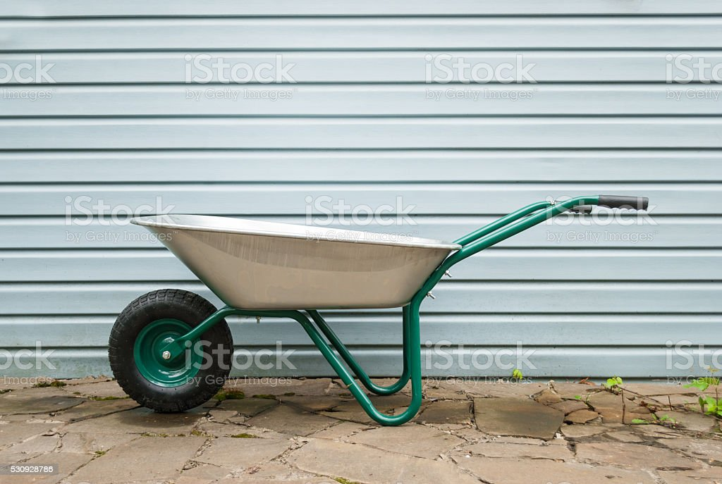 Construction wheelbarrow near the wall on the street. stock photo