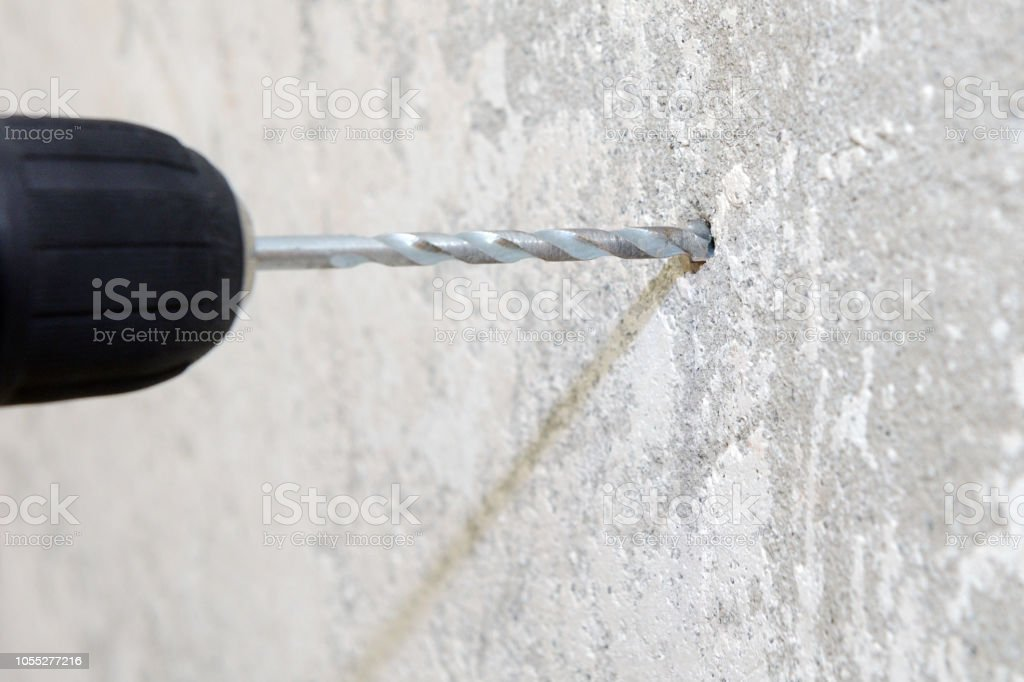 image of construction work, electric drill drills a hole in the wall,...