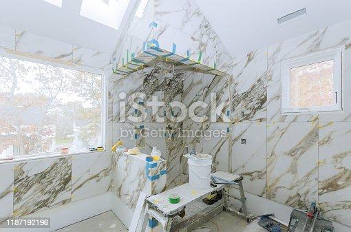 1138442636 istock photo Construction work installing ceramic tile on reconstruction of bathroom 1187192196