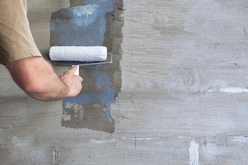 Construction work, plastering and wall priming. Builder's hand with paint roller. Copy space