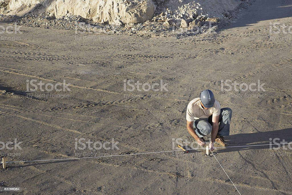 Construction worker adjusting string outline on construction site royalty free stockfoto