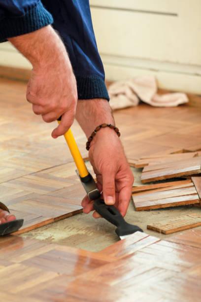 O trabalhador e o construtor da construção estão trabalhando na renovação do apartamento. O trabalhador manual está removendo o revestimento de madeira velho do parquet usando o martelo amarelo e a ferramenta de raspagem. O Construtor Desagrupa o ass - foto de acervo