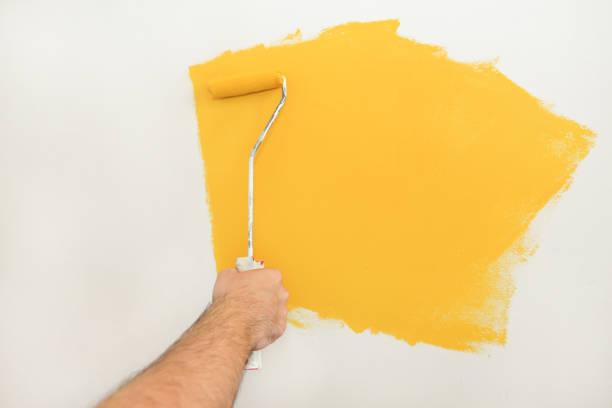Trabalhador da construção e trabalhador manual que fazem a renovação do revestimento no apartamento. Pintor profissional que usa a pintura da escova do rolo de pintura da parede com cor amarela no canteiro de obras. Conceito Home da renovação. - foto de acervo