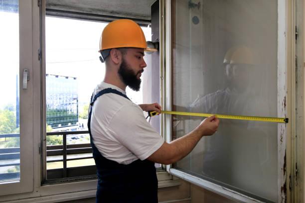 O trabalhador da construção e o trabalhador manual estão trabalhando na renovação do apartamento. O Construtor está medindo a janela usando a fita da medida no canteiro de obras. Conceito da renovação da casa. Construção e ferramentas de serviço - foto de acervo
