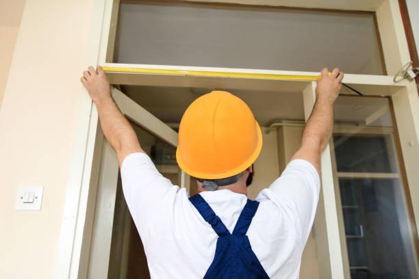 O trabalhador da construção e o trabalhador manual estão trabalhando na renovação do apartamento. O Construtor está medindo da porta do quarto usando a fita da medida no canteiro de obras. Conceito da renovação. Construção e ferramentas de servi� - foto de acervo