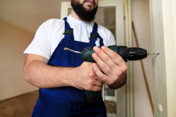 O trabalhador da construção e trabalhador manual trabalham na renovação do apartamento. O construtor com broca elétrica perfura o furo do prego na porta de madeira da parede no canteiro de obras. Conceito Home da renovação. Ferramenta de construçã - foto de acervo