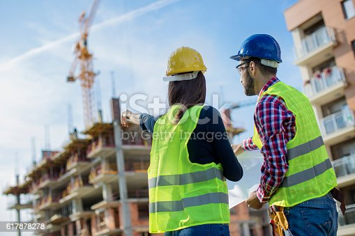 617878058 istock photo Construction worker and his manager looking at blueprints 617878278
