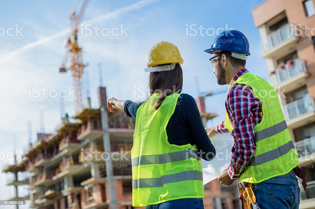 Construction worker and his manager looking at blueprints stock photo