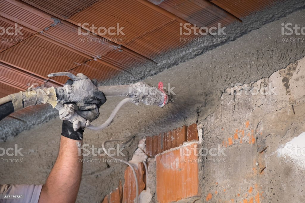 Construction worker applying cement plaster stock photo