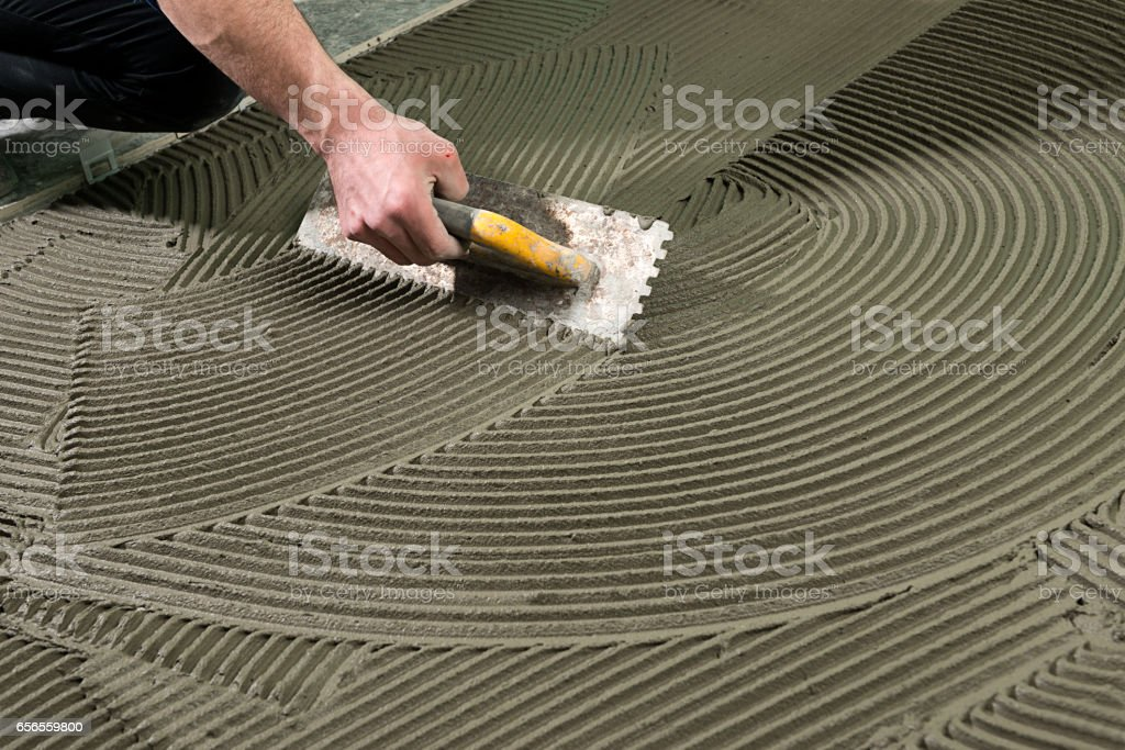 Construction Worker Applying Ceramic Glue stock photo