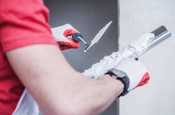 Construction Worker Applying Drywall Compound On Taping Knife. stock photo