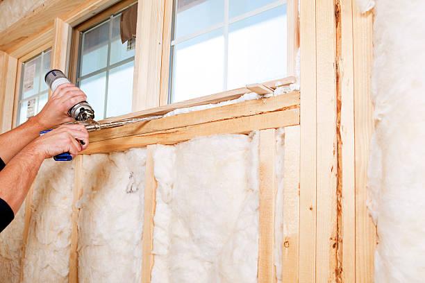 operaio edile applicazione espandibile materiale espanso isolante su window (finestra) - gommapiuma foto e immagini stock