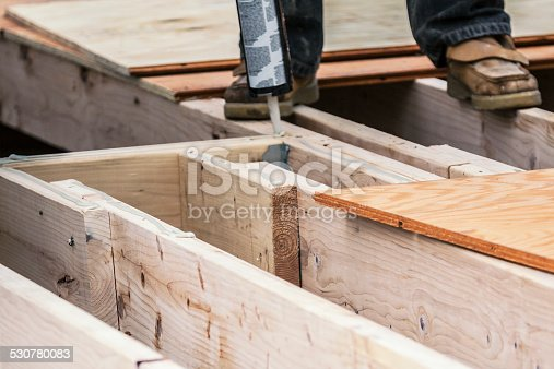 istock Construction Worker Applying Industrial Wood Glue To Subfloor Beams 530780083