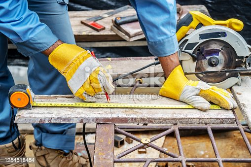 693910734 istock photo Construction worker are using tape measurements to measure planks and pencil are used to write, Close up of male hands measuring wood flooring, Construction industry, housework do it yourself. 1254518454