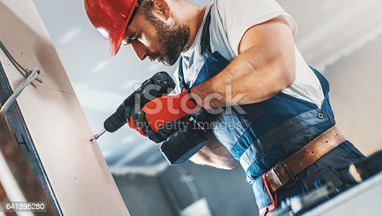 Closeup side view of a handsome 30's construction worker screwing bolts into drywall plates. He's using electric screwdriver, wearing blue uniform with a toll belt and red helmet and gloves.