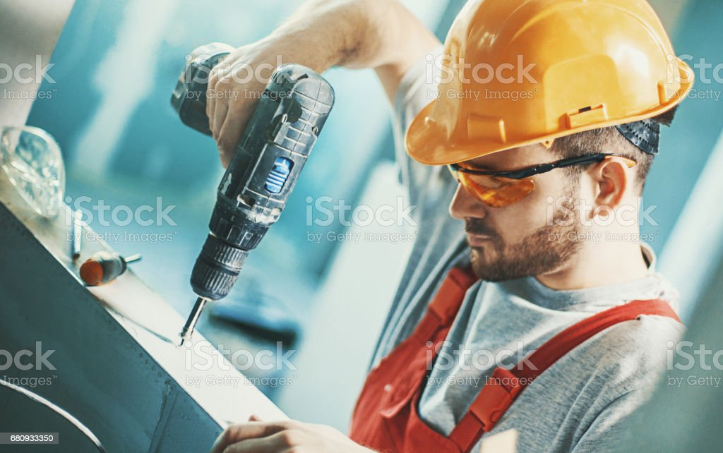 Construction worker assembling a drywall. stock photo