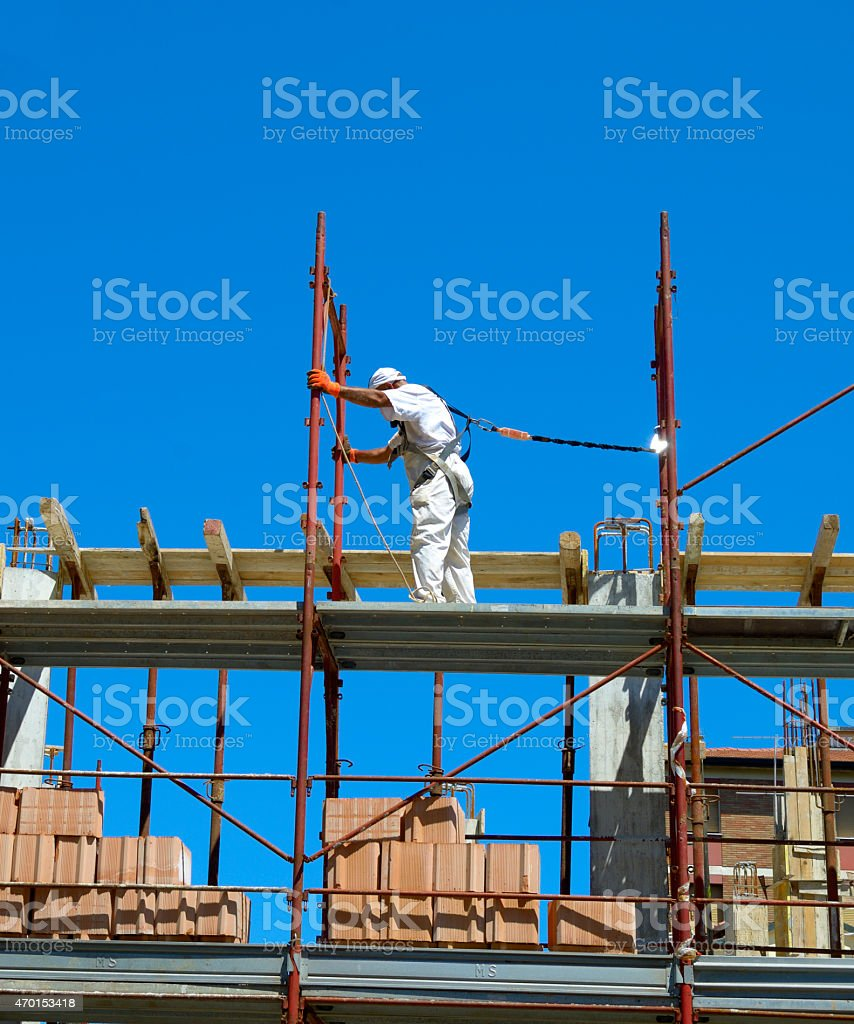Construction worker assembling scaffolding on building site stock photo