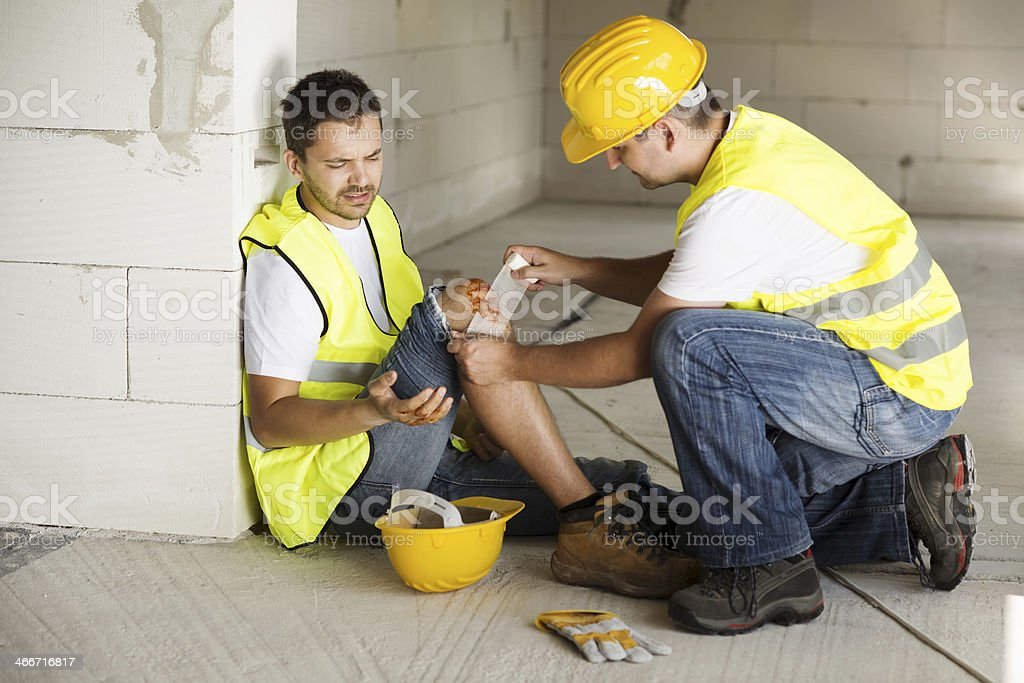 Construction worker assisting injured coworker stock photo