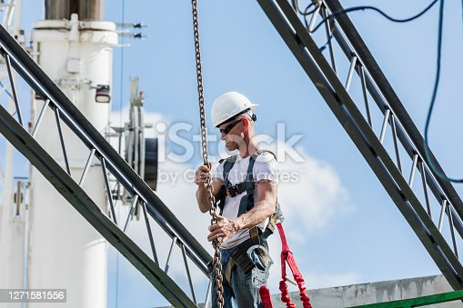 A mature man working at a construction site. He is high up in the air, on a scissor lift, a steel worker installing roof joists or trusses.