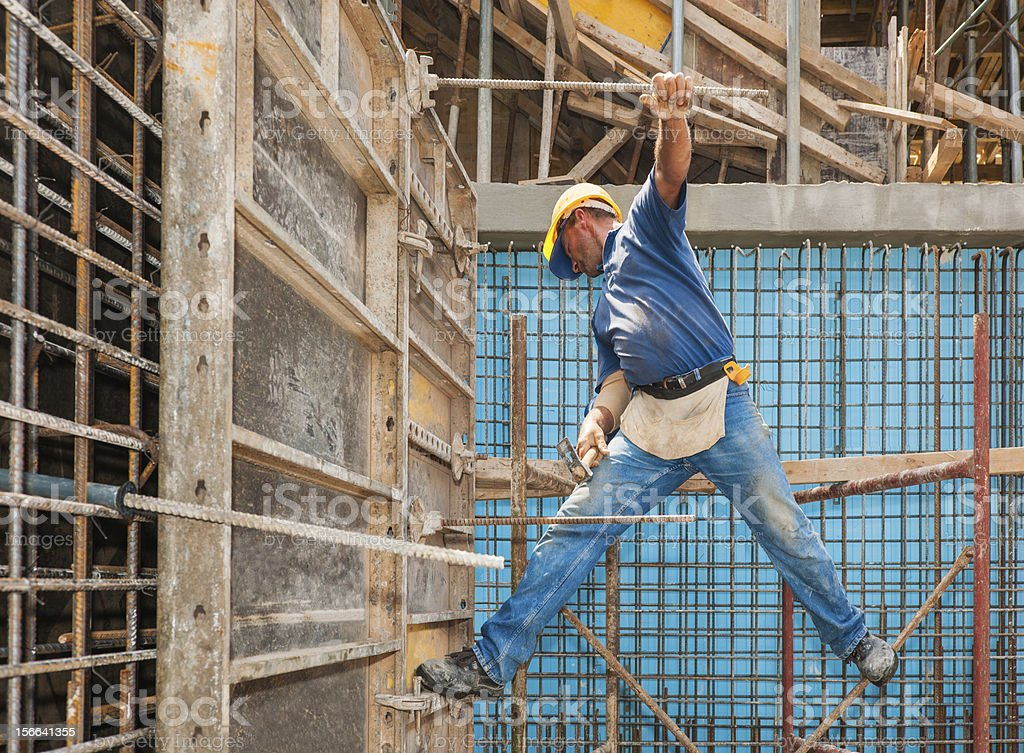 Construction worker balancing between scaffold and formwork frame stock photo