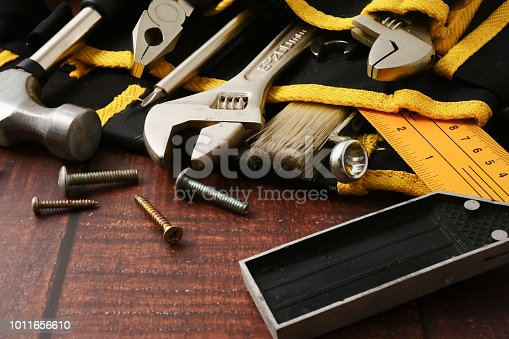 istock Construction worker belt with tools on wooden table background. 1011656610