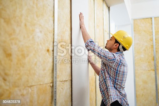 Construction worker on construction site building up a drywall.