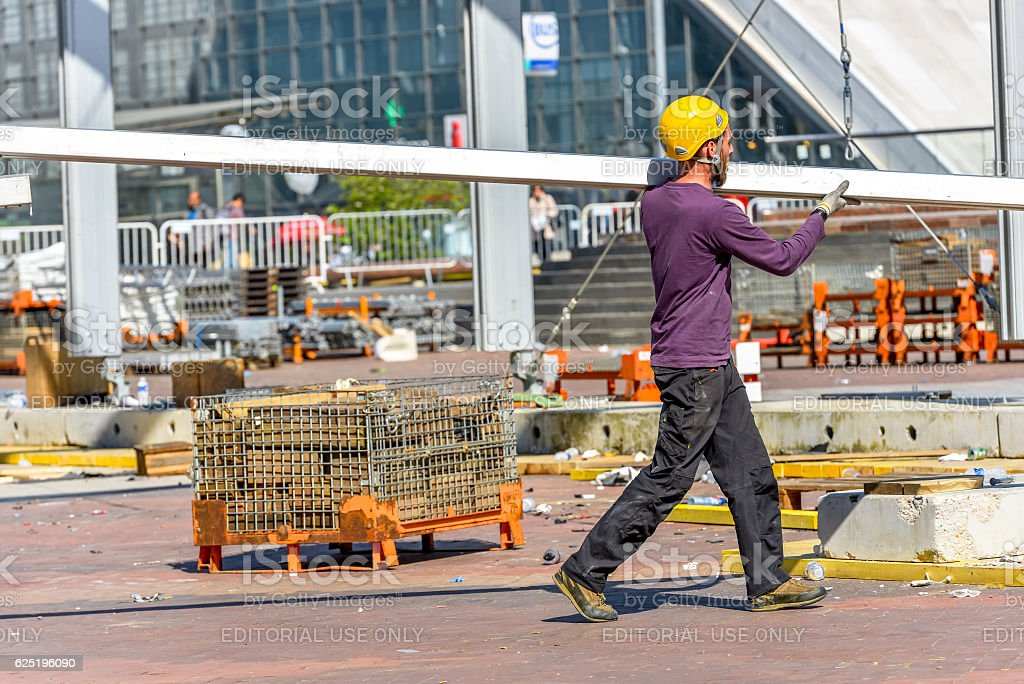 Construction worker carrying a steel beam stock photo