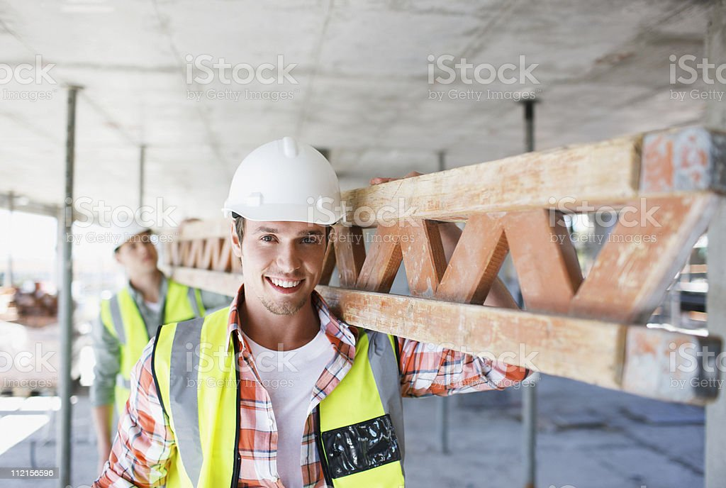 Construction worker carrying girder on construction site stock photo