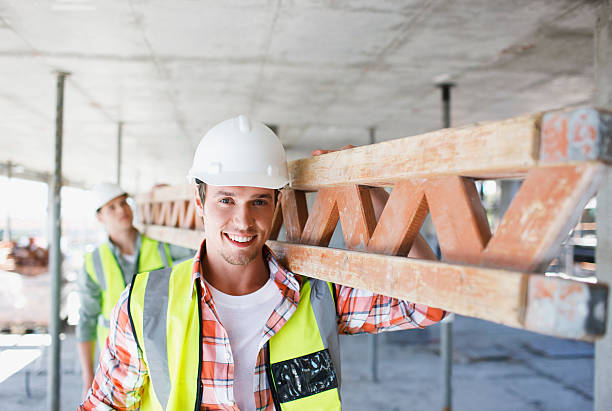 construction worker carrying girder on construction site - builders stock photos and pictures
