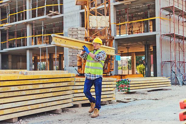 construction worker carrying planks - matériau de construction photos et images de collection