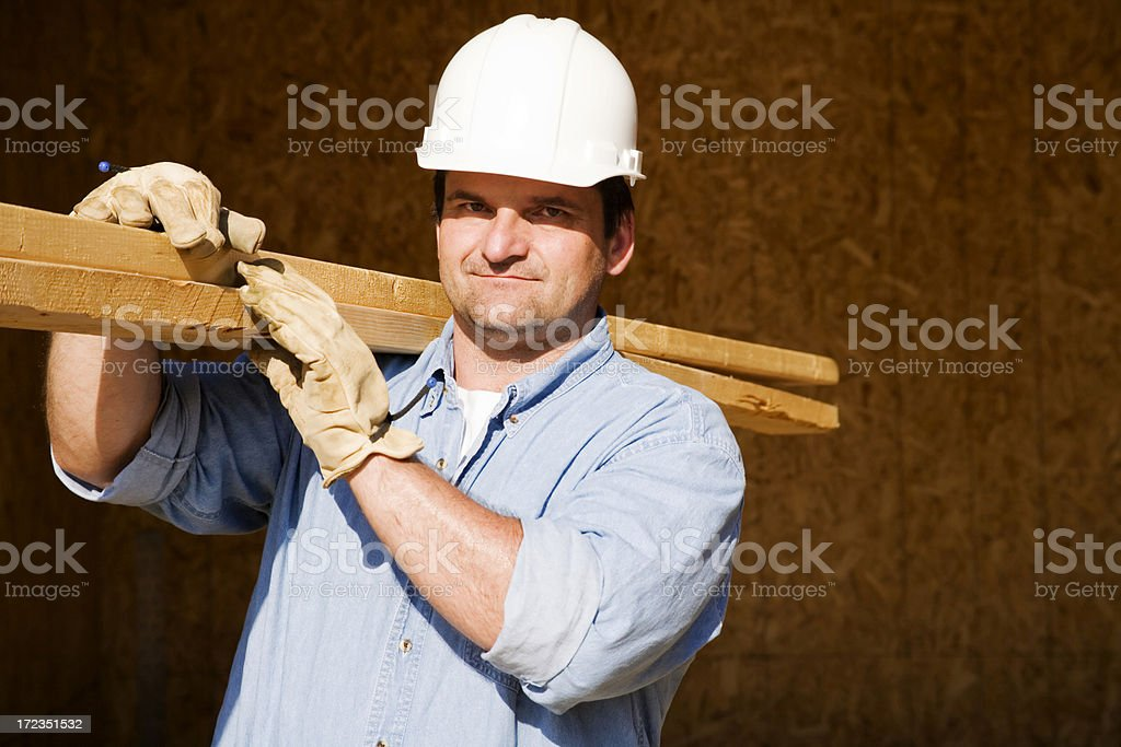 Construction Worker Carrying Wooden Planks royalty-free stock photo
