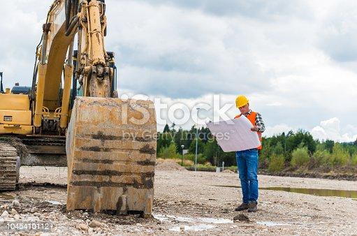 istock Construction worker checking blueprint 1045410112