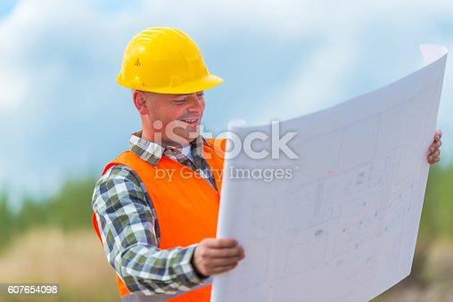 istock Construction worker checking blueprint 607654098