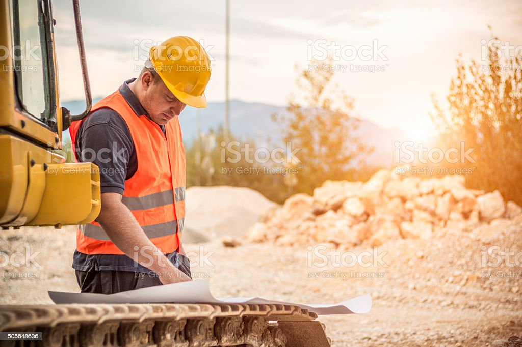 Construction worker checking blueprints stock photo