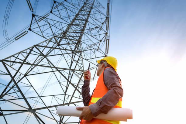 pracownik budowlany sprawdza lokalizację w pobliżu wieży wysokiego napięcia. - przewód składnik elektryczny zdjęcia i obrazy z banku zdjęć