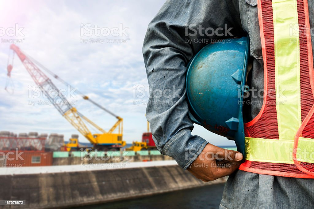 construction worker checking location site with crane on the background stock photo