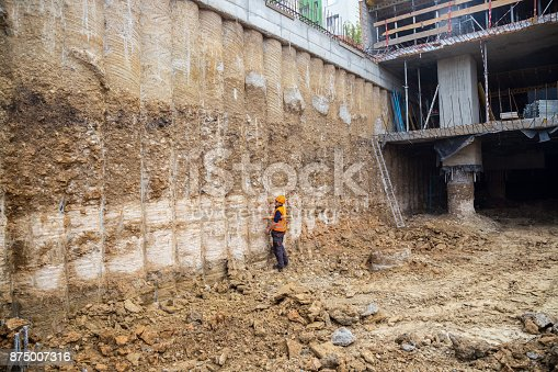 Construction worker checking pile retaining wall